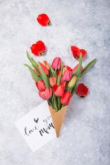 Lody czerwonych kwiatów tulipanów w waflowym stożku z kartą kocham cię mamo na betonowym blacie w stylu płaskiej płaskiej.