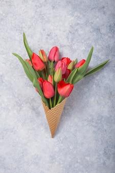 Lody czerwonych tulipanów kwiaty w rożku waflowym na betonowym blatowym widoku w stylu płaskiej świeckich.