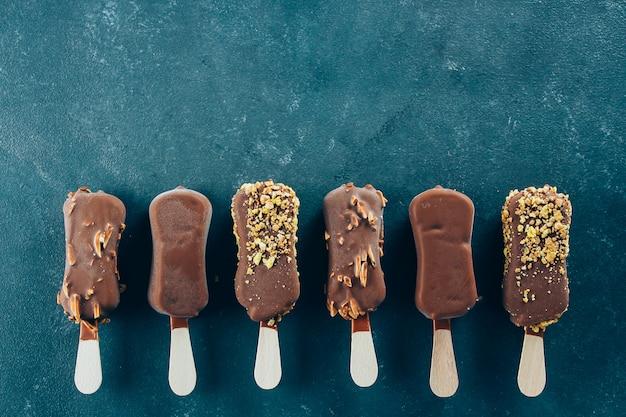 Lody eskimo w polewie czekoladowej na niebieskim tle. pyszne przekąski słodkiej żywności.