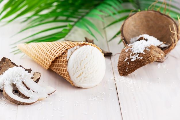 Lody kokosowe z gałązką palmową na białym drewnianym stole