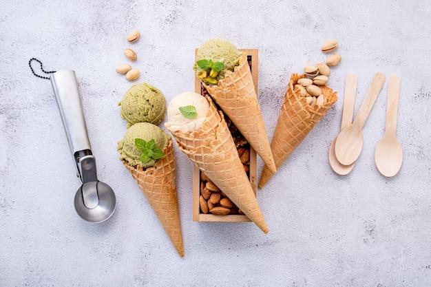 Lody pistacjowe i waniliowe w misce z konfiguracją mieszanych orzechów na białym tle kamienia
