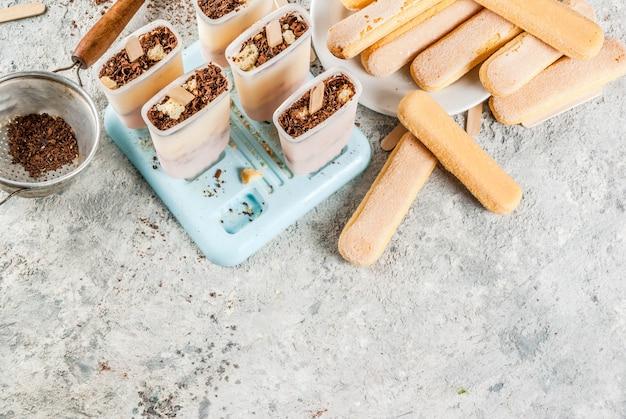Lody popsicles tiramisu. gelato wyskakuje z włoskimi ciasteczkami savoiardi
