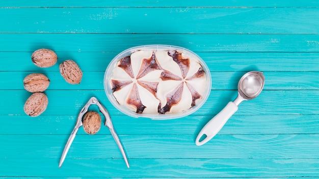 Lody w plastikowej misce z łyżeczką i orzechami włoskimi z dziadkiem do orzechów