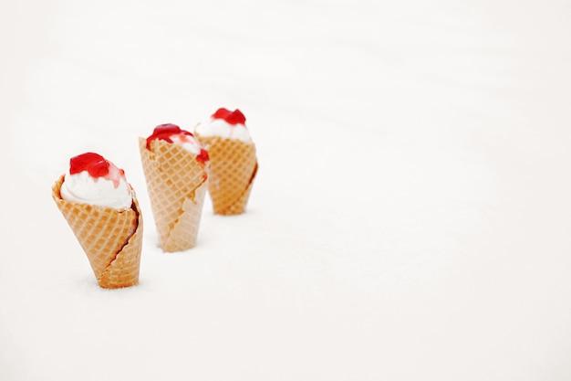 Lody w rożkach waflowych z czerwoną galaretką w śniegu