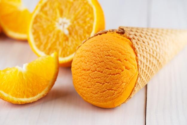Lody w rożku waflowym z plastrami pomarańczy na drewnianym stole
