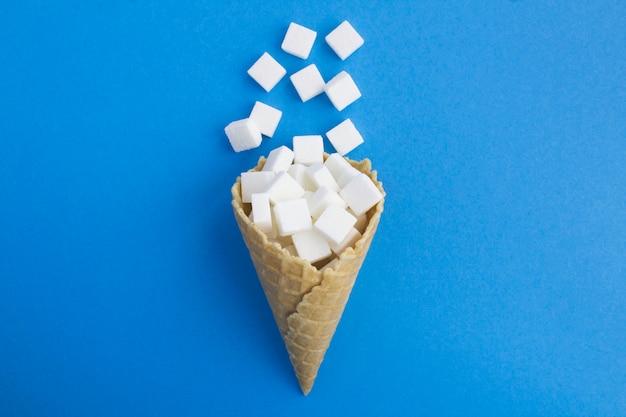 Lody w rożku z białym cukrem na środku niebieskiego stołu. widok z góry.