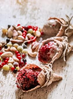 Lody waflowy rożek z jagodami na drewnianym stole