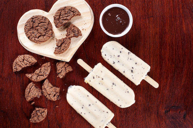 Lody waniliowe oblane białą czekoladą i wypełnione kremem z orzechów laskowych. lód na patyku. widok z góry