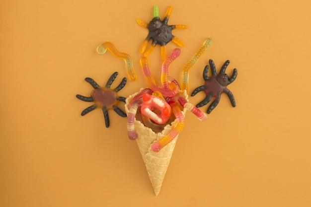 Lody z cukierkami na halloween na pomarańczowym stole. widok z góry.