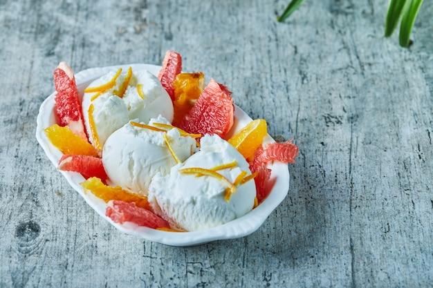 Lody z grejpfrutem i plasterkami pomarańczy w białej misce