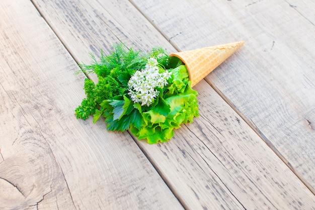 Lody ze świeżych ziół na drewnianym. sałata, pietruszka, koperek, kwiat czosnku.