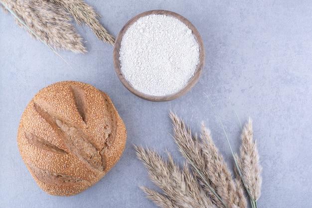 Łodygi suszonej trawy z piór, bochenek chleba i miska na mąkę na marmurowej powierzchni