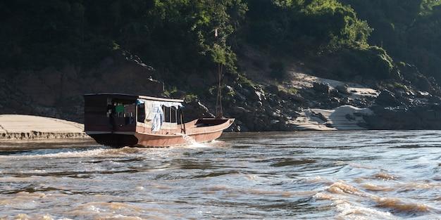 Łódź mieszkalna podróżuje wzdłuż rzeki mekong, laos