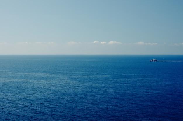 Łódź na błękitnym morze powierzchni widok z lotu ptaka. charakter tła