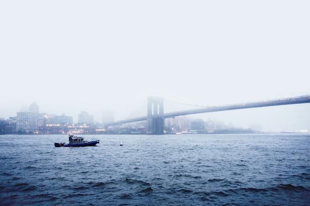 Łódź na wodzie w pobliżu mostu wantowego podczas mglistej pogody