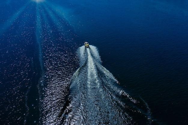 Łódź odpływa na falach błękitnego morza, przecinając je