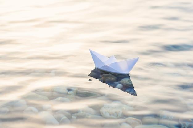 Łódź origami białego papieru na niebieskiej głębokiej wodzie.