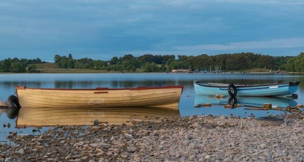 Łódź po jeziorze w pobliżu miasta mullingar w irlandii z odbiciem w wodzie o zachodzie słońca