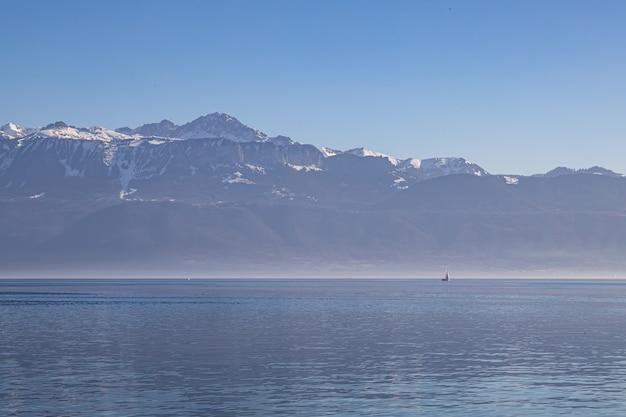 Łódź po zamglonym, zamglonym jeziorze genewskim i alpach widzianych z lozanny w szwajcarii