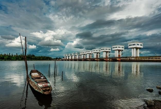 Łódź rybacka i wodna bariera i rzeka z burzowym niebem