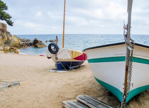 Łódź rybacka łęk na niebieskiego nieba i morza plażowym tle. plaża z łodziami w pobliżu wybrzeża lloret de mar.