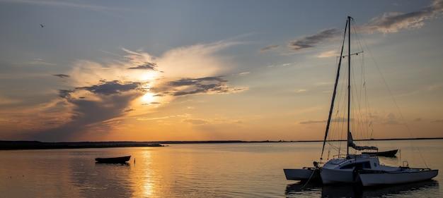 Łódź rybacka na jeziorze o zachodzie słońca.