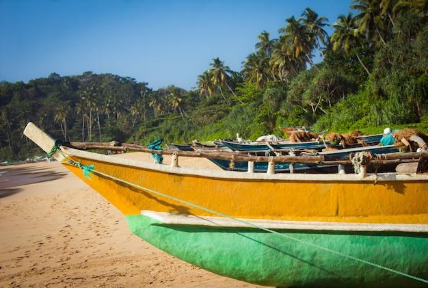 Łódź rybacka na tropikalnej plaży z palmami