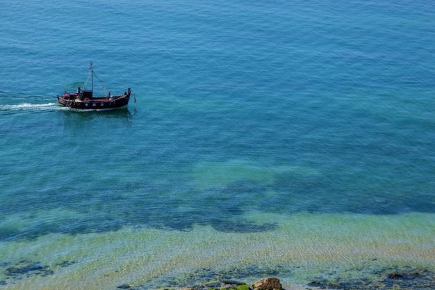 Łódź rybacka płynie wzdłuż wybrzeża morza czarnego