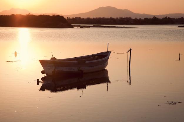 Łódź rybacka w jeziorze przy zmierzchem