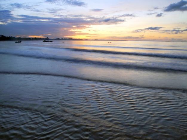 Łódź rybacka w morzu przy wschodem słońca