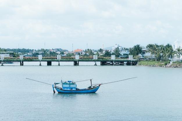 Łódź rybacka w morzu z mostem behind