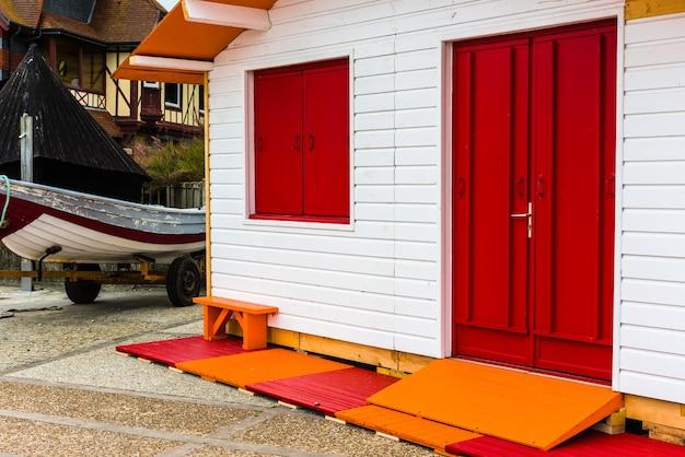Łódź rybacka w pobliżu białego drewnianego wiejskiego domu z czerwonymi drzwiami i oknem