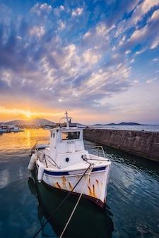 Łódź rybacka w porcie naousa na zachód słońca. paros lsland, grecja