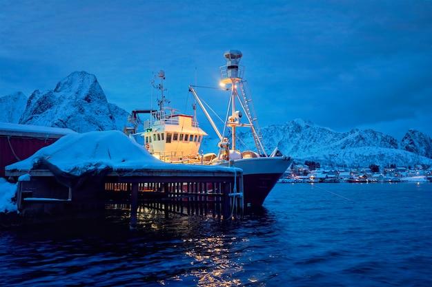 Łódź rybacka w reine wiosce przy nocą. lofoty, norwegia
