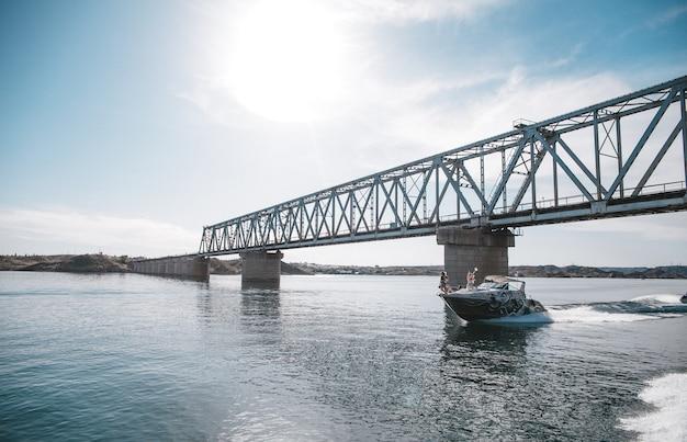 Łódź unosi się na wodzie pod mostem w pogodny letni dzień.