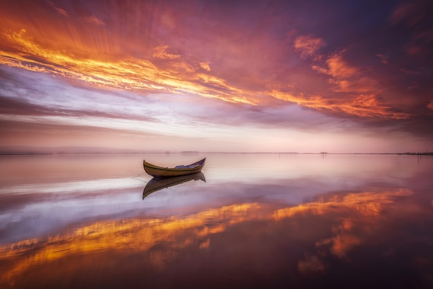 Łódź w jeziorze o zachodzie słońca