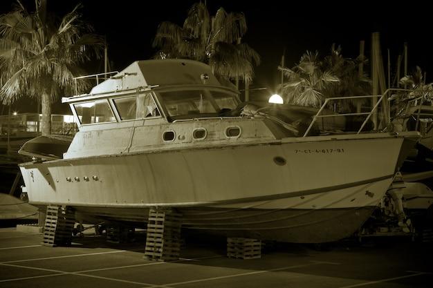Łódź w suchym doku wewnątrz portu otoczona palmami w ujęciu monochromatycznym i nocnym