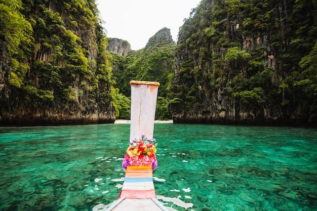 Łódź z długim ogonem unosząca się w przezroczystej wodzie wyspy phi phi, maya bay, rajskiej wyspy thailandia.
