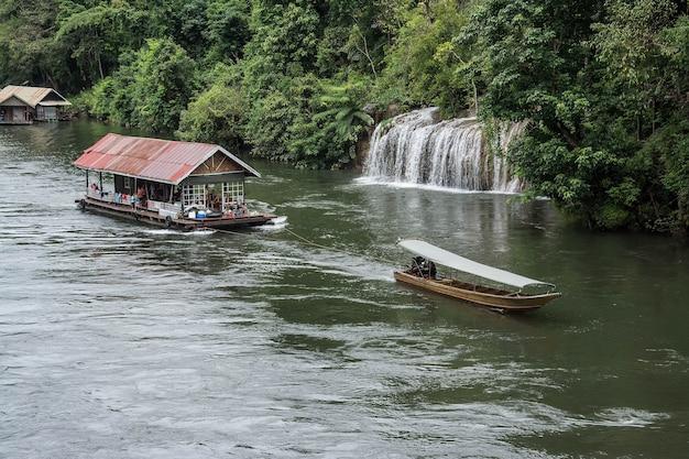 Łódź z długim ogonem z pływającym domem w rzece kwai sai yok yai wodospad kanchanaburi w tajlandii
