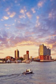 Łódź z turystami płynie w kierunku elbphilharmonie w hamburgu o zachodzie słońca