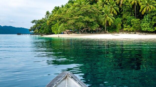 Łódź zbliża się do miejscowej wioski na wyspie friwen, papuas zachodni, raja ampat, indonezja