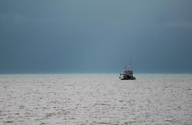 Łodzi rybackiej żeglowanie pod burzowym niebem, zatoka tajlandia