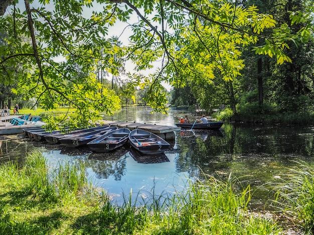 Łodzie na molo w parku miejskim. summer park z jeziorem. zadokowana drewniana łódź wiosłowa.
