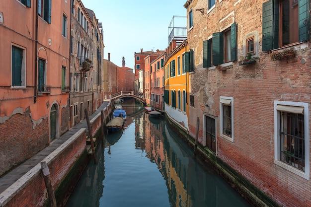 Łodzie na wąskim kanale pomiędzy kolorowymi, zabytkowymi domami w wenecji.