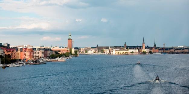 Łodzie poruszające się w zatoce z budynkami w tle, stockholm town hall, riddarfjarden, sztokholm, szwecja