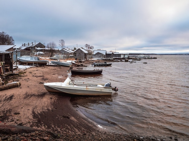 Łodzie rybackie na wybrzeżu morza białego. wioska rybacka rabocheostrovsk na brzegu morza białego podczas odpływu.