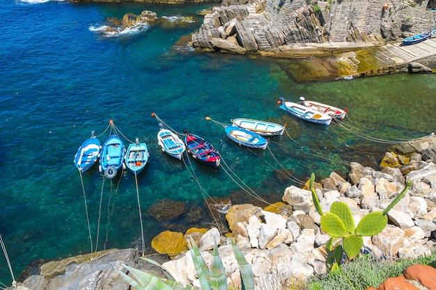 Łodzie rybackie pływające po morzu śródziemnym w porcie w cinque terre we włoszech.