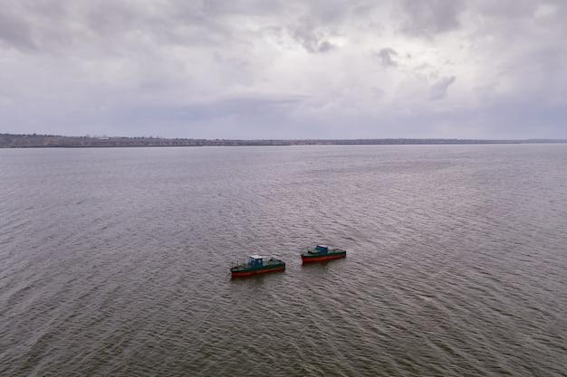 Łodzie rybackie, pływające po spokojnych wodach i wędrujące pod niebem z chmurami