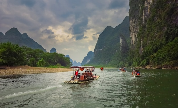 Łodzie toczą turystów po rzece. rzeka li (lijiang) znajduje się w guilin w prowincji guangxi w południowych chinach.