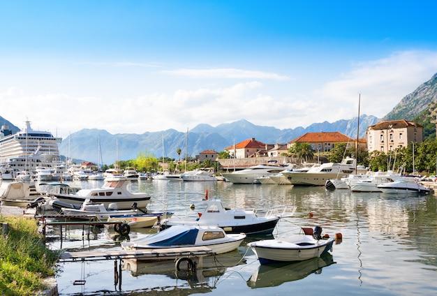 Łodzie w morzu przy zmierzchem z górami i starym miastem